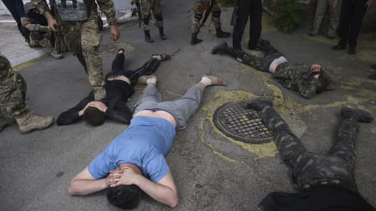 Ukrainian troops from battalion Azov ground men detained at the site of a battle with pro-Russian fighters in Mariupol, eastern Ukraine, Friday, June 13, 2014.